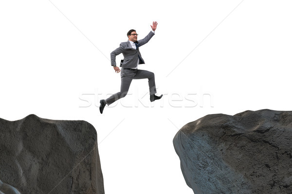 Stock photo: Ambitious businessman jumping over the cliff