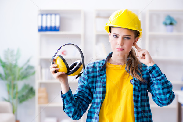 Stock photo: Woman in workshop with noise cancelling headphones