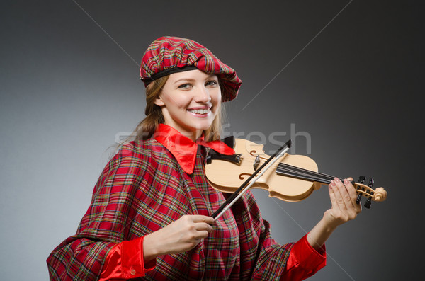 Stock photo: Woman in scottish clothing in musical concept