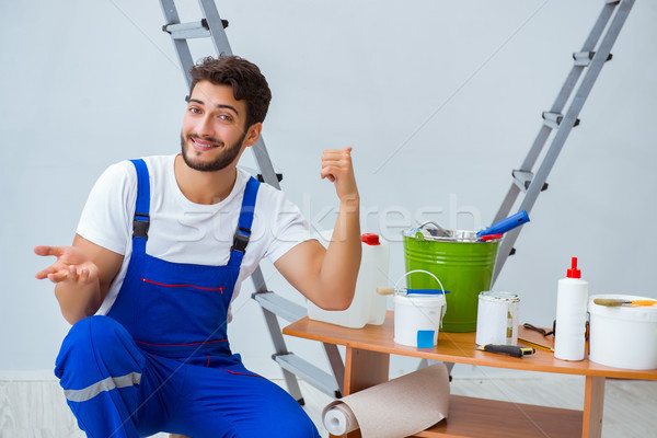 Repairman doing renovation repair in the house with paper wallpa Stock photo © Elnur