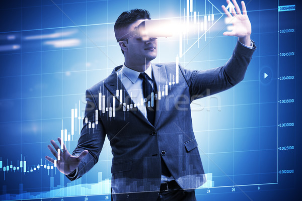 Businessman in virtual reality trading on stock market Stock photo © Elnur
