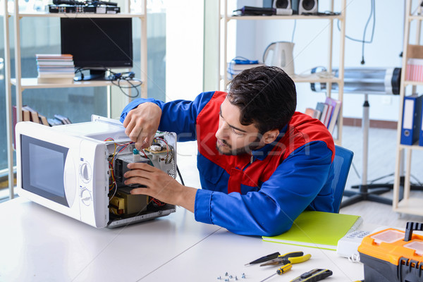 The young repairman fixing and repairing microwave oven Stock photo © Elnur