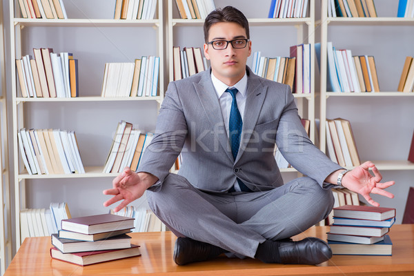 Businessman student in lotus position concentrating  in the libr Stock photo © Elnur