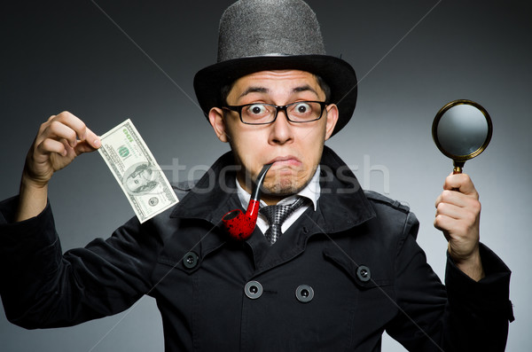 Young detective in black coat with money against gray Stock photo © Elnur