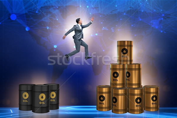 Stock photo: Businessman jumping from stack of oil barrels