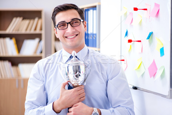 Young businessman receiving prize cup in office Stock photo © Elnur