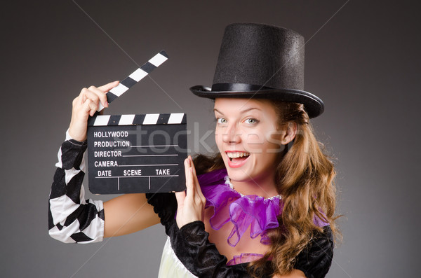 Pretty girl in jester costume holding clapperboard against gray Stock photo © Elnur