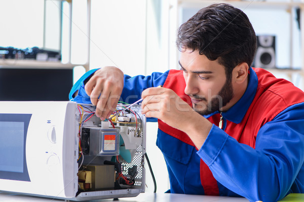 Young repairman fixing and repairing microwave oven Stock photo © Elnur