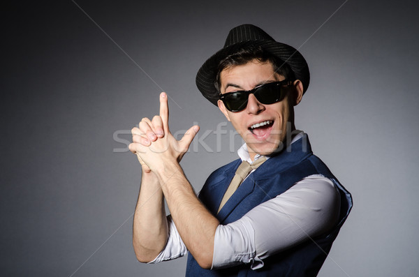Stock photo: Young man in blue vest and hat against gray