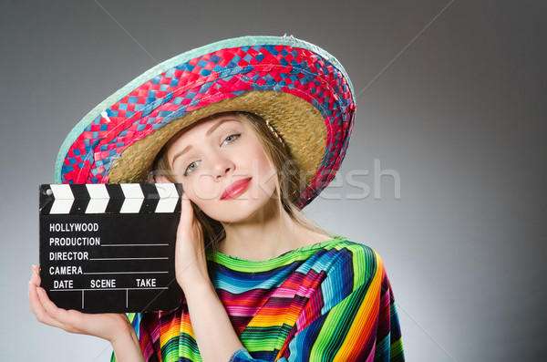 Girl in mexican vivid poncho holding clapboard against gray Stock photo © Elnur