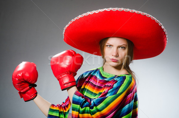 Girl in mexican vivid poncho and box gloves against gray Stock photo © Elnur