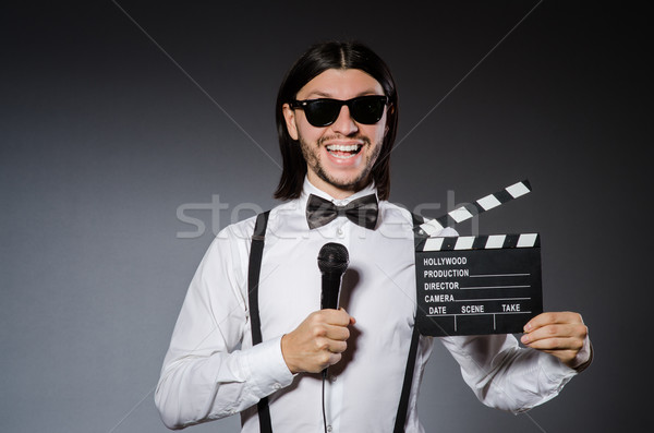 Positive man holding clapperboard and microphone isolated on gray Stock photo © Elnur