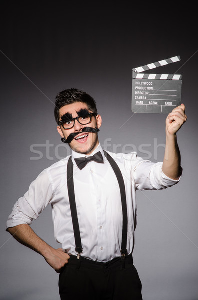 Young caucasian man with false moustache and clapperboard agains Stock photo © Elnur