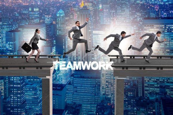 Teamwork concept with business people crossing bridge Stock photo © Elnur