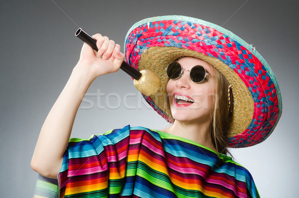 Stock photo: Girl in mexican vivid poncho with maracas against gray