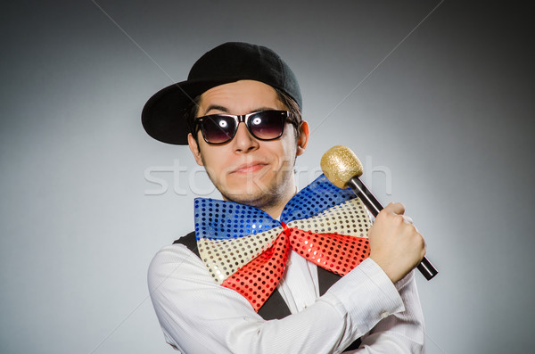 Stock photo: Funny man with mic in karaoke concept