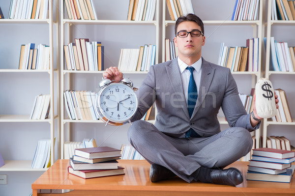 Stock photo: Businessman student in lotus position with an alarm clock and a