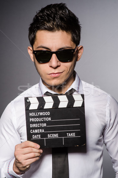Young caucasian man with clapperboard against gray Stock photo © Elnur