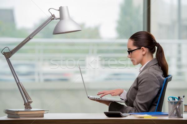 Businesswoman working at her desk Stock photo © Elnur