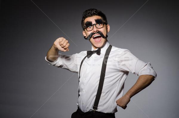 Young caucasian man with false moustache against gray Stock photo © Elnur