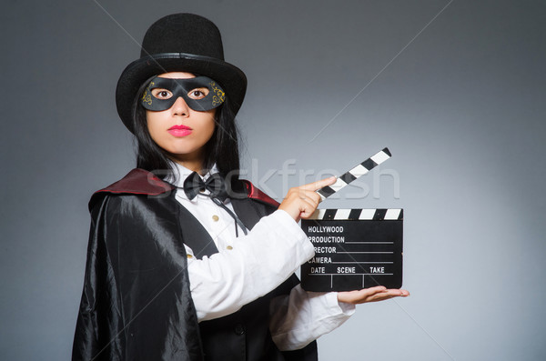 Woman wearing mask with movie board Stock photo © Elnur