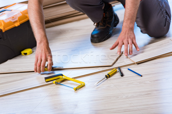 Man laying laminate flooring in construction concept Stock photo © Elnur