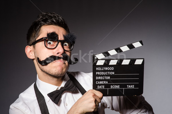Young man with false moustache holding clapperboard isolated on  Stock photo © Elnur