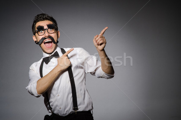 Young caucasian man with false moustache against gray Stock photo © Elnur