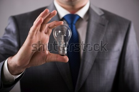 Businessman holding light bulb in creativity concept Stock photo © Elnur