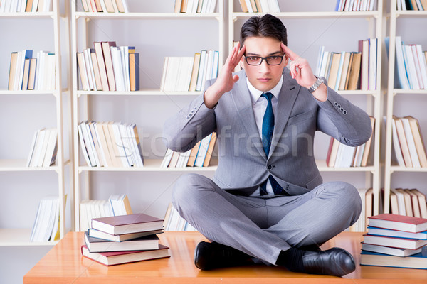 Stock photo: Businessman student in lotus position concentrating  in the libr