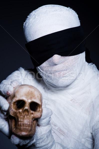 Stock photo: Mummy with skull in dark room