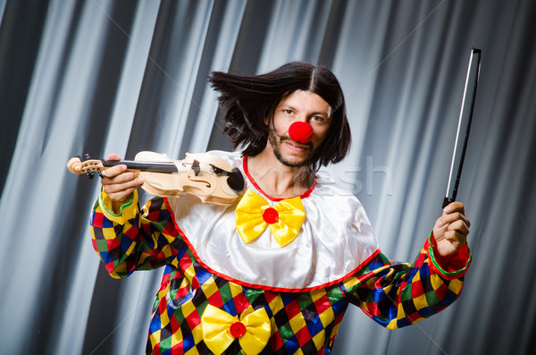 Funny clown plyaing violin against curtain Stock photo © Elnur