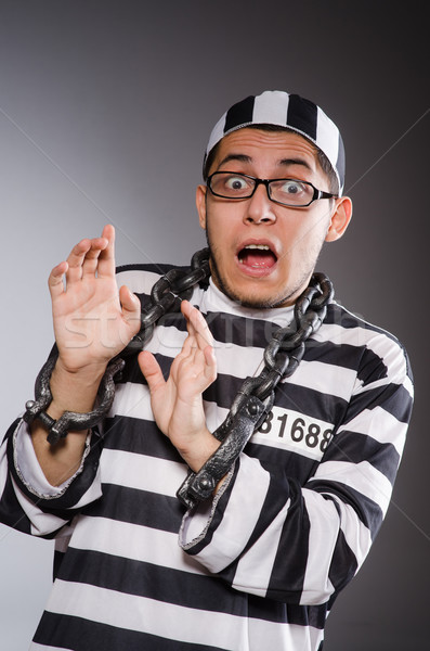 Young prisoner in chains against gray Stock photo © Elnur