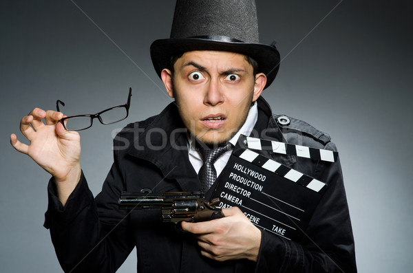 Young man with weapon and clapboard against gray Stock photo © Elnur