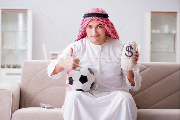 Young arab man watching football sitting on sofa Stock photo © Elnur