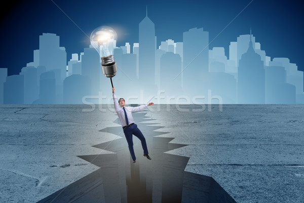 Businessman flying over gap on light bulb balloon Stock photo © Elnur