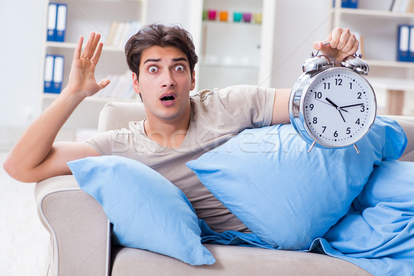 Man having trouble waking up with alarm clock Stock photo © Elnur