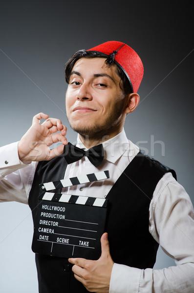 Man with movie board wearing fez hat Stock photo © Elnur