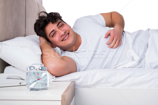 Homme lit souffrance insomnie heureux horloge Photo stock © Elnur