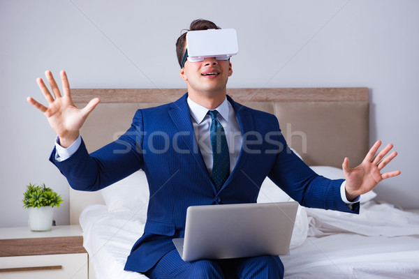 Businessman wearing a virtual reality headset in the bedroom Stock photo © Elnur