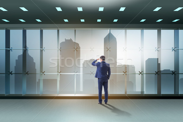 Businessman in front of office window thinking of new challenges Stock photo © Elnur