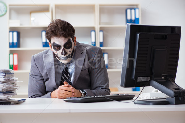 Businessmsn with scary face mask working in office Stock photo © Elnur