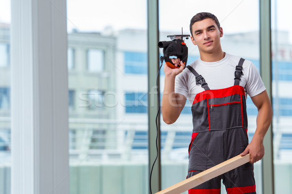 Young carpenter working at construction site Stock photo © Elnur