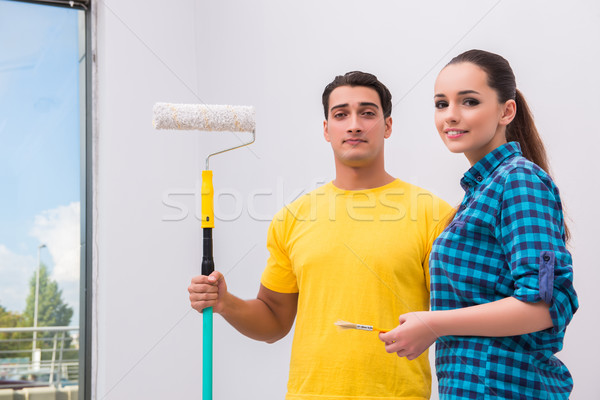 Stock photo: Young couple painting wall at home