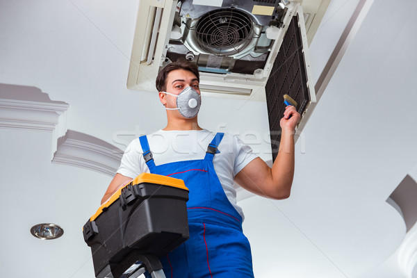 Stock photo: Worker repairing ceiling air conditioning unit