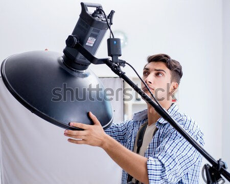 Young photographer working in photo studio Stock photo © Elnur