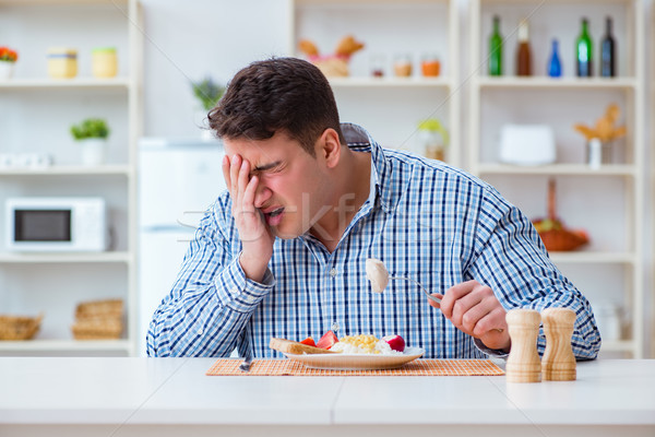 Man eating tasteless food at home for lunch Stock photo © Elnur