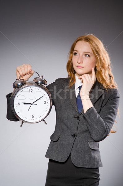 Businesswoman with clock being late for her deliverables Stock photo © Elnur