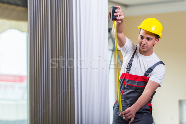 Young repairman with tape measure working on repairs Stock photo © Elnur