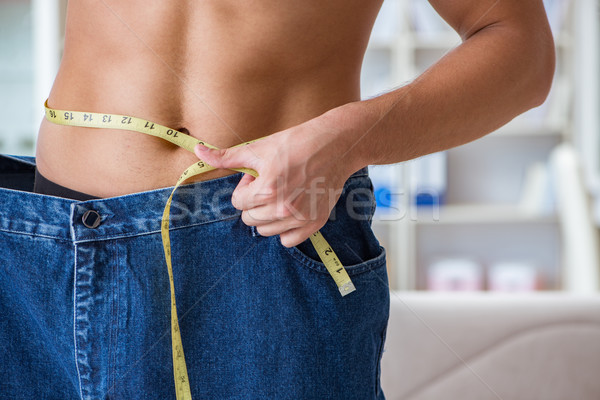 The man in oversized pants in weight loss concept Stock photo © Elnur